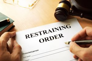 Picture of a man completing a restraining order document